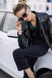 Fashion outdoor photo of beautiful woman with dark hair in black leather jacket and sunglasses posing in luxurious auto Stock Photo