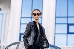 Fashion outdoor photo of sexy beautiful woman with dark hair in black leather jacket and sunglasses posing in luxurious auto Stock Photo