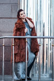 Fashion outdoor photo of glamour woman with dark hair wearing luxurious fur coat and leather gloves,posing Stock Images