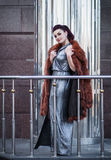 Fashion outdoor photo of sexy glamour woman with dark hair wearing luxurious fur coat and leather gloves Royalty Free Stock Photos