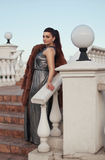 Fashion outdoor photo of sexy glamour woman with dark hair wearing luxurious fur coat and leather gloves Royalty Free Stock Images
