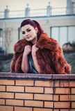 Fashion outdoor photo of sexy glamour woman with dark hair wearing luxurious fur coat and leather gloves Royalty Free Stock Image
