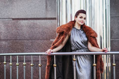 Fashion outdoor photo of sexy glamour woman with dark hair wearing luxurious fur coat and leather gloves Royalty Free Stock Photography
