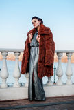 Fashion outdoor photo of sexy glamour woman with dark hair wearing luxurious fur coat and leather gloves Royalty Free Stock Photo