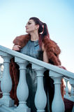 Fashion outdoor photo of sexy glamour woman with dark hair wearing luxurious fur coat and leather gloves Stock Image