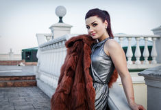 Fashion outdoor photo of sexy glamour woman with dark hair wearing luxurious fur coat and leather gloves Stock Images