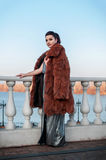 Fashion outdoor photo of sexy glamour woman with dark hair wearing luxurious fur coat and leather gloves Stock Photo
