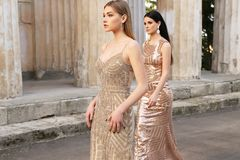 Beautiful young women with dark hair in luxurious evening dresses. Fashion outdoor photo of two beautiful girls with dark hair in luxurious evening dresses stock images