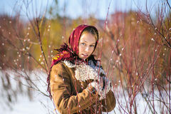 Fashion outdoor portrait of beautiful blonde woman clothed in scarf and sheepskin coat among blooming willow willows Stock Photography