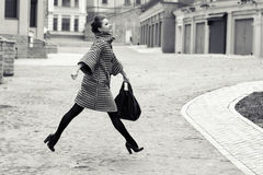 Fashion and people concept - happy young woman or teenage girl running and jumping high on city street Royalty Free Stock Photography