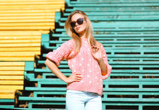Fashion and people concept - pretty blonde in sunglasses posing Stock Images