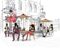 Fashion people in the street cafe. Street cafe with flowers in the old city. Waiters serve the tables Royalty Free Stock Photos