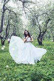 Fashion, people and summer holidays concept. Beautiful woman in hat and dress sunbathing over green blooming garden background stock image