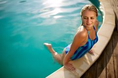 Fashion photo of attractive slim woman with long blond hair in elegant striped body swimsuit relaxing in swimming pool Stock Photo