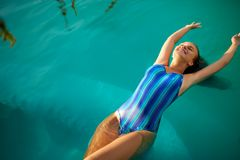 Fashion photo of attractive slim woman with long blond hair in elegant striped body swimsuit relaxing in swimming pool stock photography
