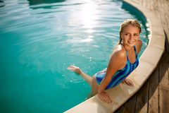 Fashion photo of attractive slim woman with long blond hair in elegant striped body swimsuit relaxing in swimming pool royalty free stock photography