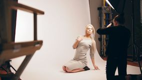 Fashion photo backstage - Blonde handsome girl posing for photographer - model sits at knees stock video footage