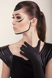 Fashion photo of beautiful asian girl with painted face. Fashion studio photo of beautiful asian look girl with painted face in elegant black dress and glove Royalty Free Stock Photos