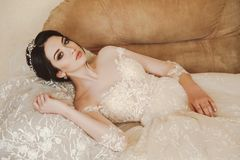 Beautiful bride in elegant wedding dress and diadem posing in r stock photo