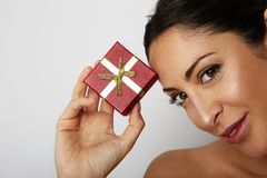 Fashion photo of a beautiful brunette woman with dark short hair holding hand gift box over white empty background. Positive human emotions, reaction, gestures stock image