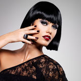 Fashion photo of a beautiful brunette woman with shot hairstyle. Closeup girl's face with red nails stock photography