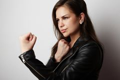 Fashion photo of a beautiful brunette woman wearing leather jacket with dark long hair posing over white empty stock photography