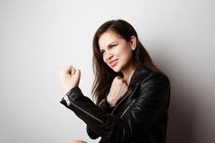 Fashion photo of a beautiful brunette woman wearing leather jacket with dark long hair posing over white empty stock images