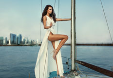 Fashion  photo of beautiful elegant woman with dark hair wearing. Luxurious white fluttering dress standing on  the yacht Stock Photography