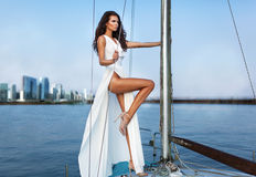 Fashion  photo of beautiful elegant woman with dark hair wearing. Luxurious white fluttering dress standing on  the yacht Royalty Free Stock Photo