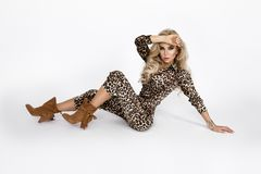 Fashion photo of a beautiful elegant young woman in a pretty jumpsuit with leopard animal print and boots posing over white. Background. Fashion photo - Image stock photography