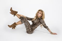 Fashion photo of a beautiful elegant young woman in a pretty jumpsuit with leopard animal print and boots posing over white. Background. Fashion photo - Image stock photos
