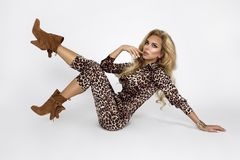 Fashion photo of a beautiful elegant young woman in a pretty jumpsuit with leopard animal print and boots posing over white. Background. Fashion photo - Image royalty free stock photos