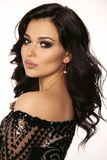 Beautiful girl with dark hair and evening makeup in luxurious bl. Fashion photo of beautiful girl with dark hair and evening makeup in luxurious black lace dress royalty free stock photo