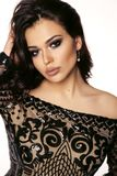 Beautiful girl with dark hair and evening makeup in luxurious bl. Fashion photo of beautiful girl with dark hair and evening makeup in luxurious black lace dress stock photos
