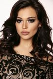 Beautiful girl with dark hair and evening makeup in luxurious bl. Fashion photo of beautiful girl with dark hair and evening makeup in luxurious black lace dress stock image