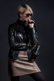 Fashion photo of beautiful lady in leather jacket and slirt with. Small handbag Stock Photo