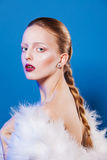 Fashion photo of beautiful lady in white feathers dress. on blue background Royalty Free Stock Image