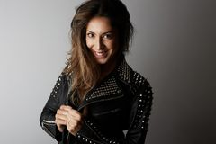Fashion photo of a beautiful smiling brunette woman wearing leather jacket with dark long hair posing over white empty. Background.Positive human emotions royalty free stock photography
