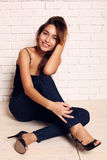Fashion photo of beautiful smiling girl with dark hair wearing jeans Royalty Free Stock Image