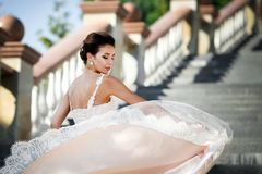 Fashion photo of beautiful woman with dark hair in luxurious wedding dress posing outdoor. stock images
