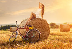 Fashion photo, beautiful woman sitting on a bale of wheat, next to the old bike Stock Photos