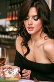 Woman with dark curly hair in elegant dress sitting in elegant r Royalty Free Stock Photo