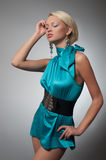 Fashion photo of a blond woman in cyan dress. Fashion photo of a blond woman in short cyan dress royalty free stock photo