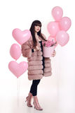 Fashion photo of fashionable woman in pink fur coat with rose bo. Uquet of flowers in hat box over balloons isolated on white studio background Royalty Free Stock Image