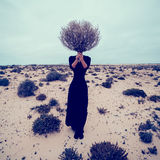 Fashion Photo. Girl in the desert with a bouquet dead branches.  Stock Photography