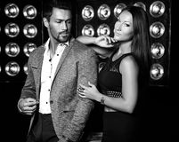 Handsome  elegant man in suit with beautiful sexy woman posing on black studio lights background. Fashion photo of handsome  elegant men in suit with beautiful Royalty Free Stock Photos