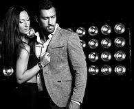 Handsome  elegant man in suit with beautiful sexy woman posing on black studio lights background. Fashion photo of handsome  elegant men in suit with beautiful Royalty Free Stock Image