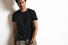 Fashion photo of a handsome man in black t-shirt. Attractive African American young man wearing a blank cotton black t-shirt isolated on white royalty free stock photo