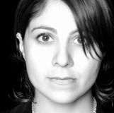 Fashion photo of a Hispanic looking girl. Moody, fashion photo of a Hispanic looking girl in black and white with hair over one eye. Slim and attractive and royalty free stock images