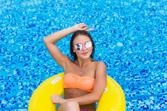 Fashion photo of sexy beautiful Girl in yellow top and sunglasses relaxing floating on inflatable ring. Outdoors lifestyle portrai. Fashion photo of sexy Stock Photography